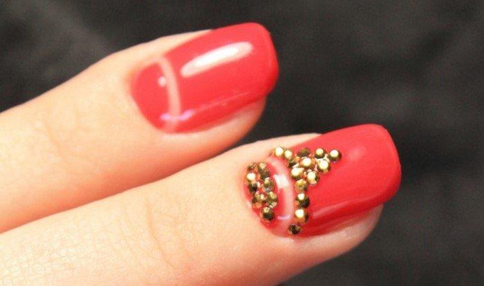 Золотые стразы на красных ногтях
