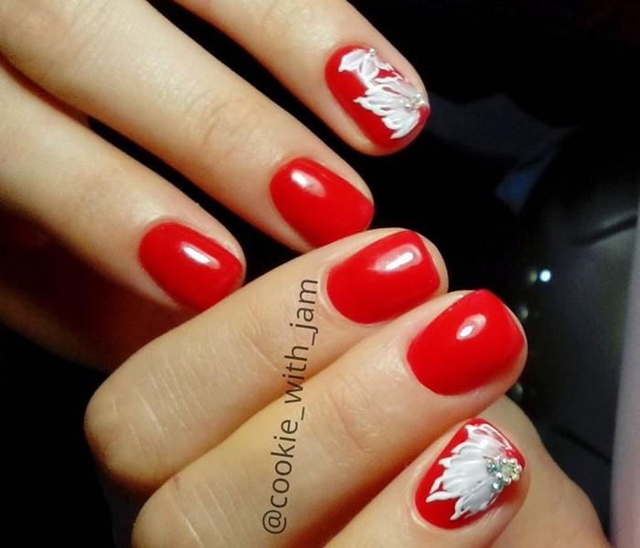 красные ногти с белым цветком и стразами
