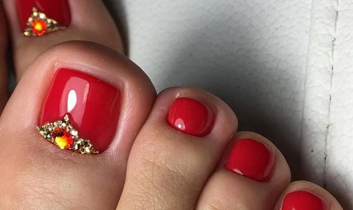 красные ногти на ногах со стразами