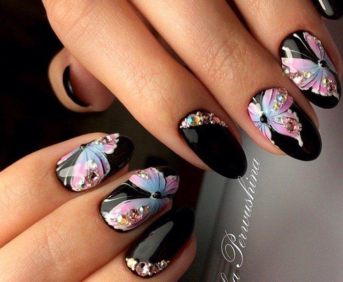 на черных ногтях бабочки со стразами