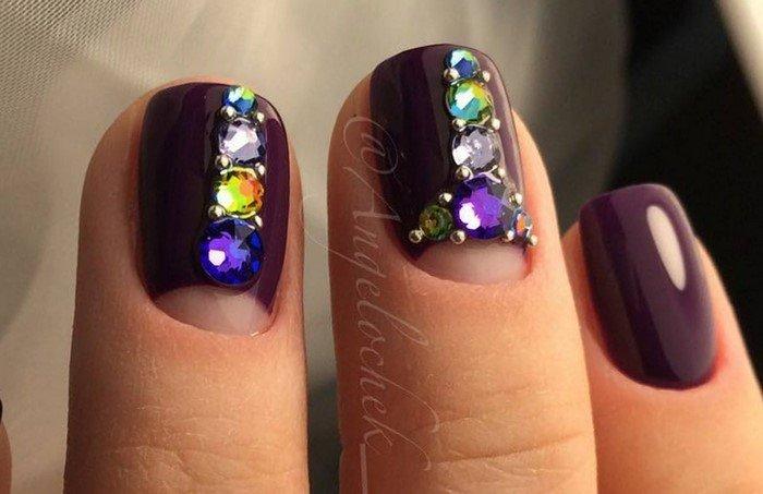 на фиолетовых ногтях разноцветные стразы