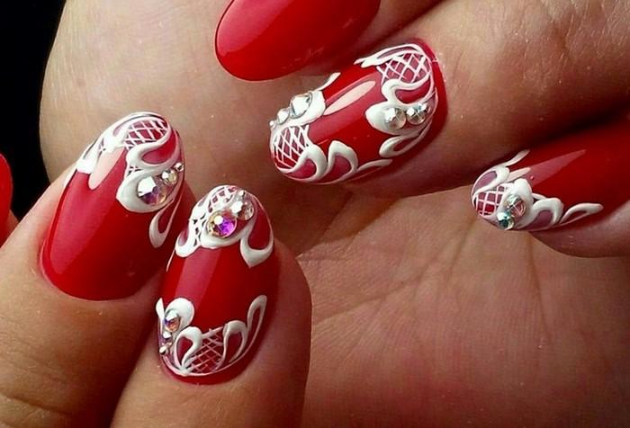 белые вензеля на красных ногтях со стразами