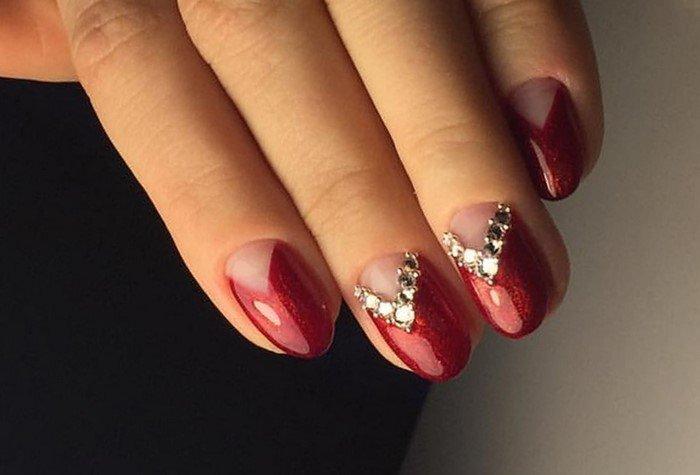 треугольная лунка из страз на красных ногтях